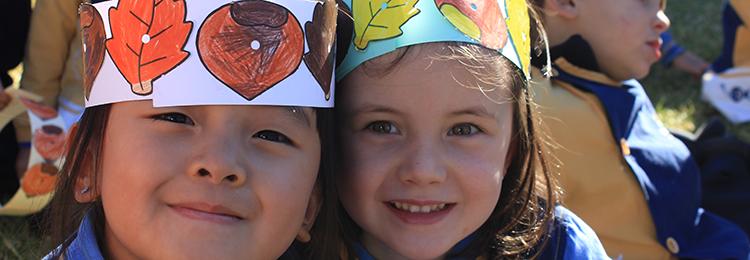 Primer plano de dos alumnas de infantil con un sombrero de papel