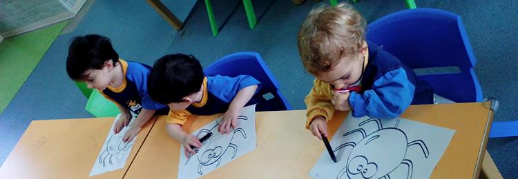 Alumnos de infantil pintando sobre una mesa