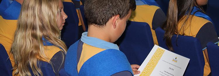 Alumno de primaria sujetando un diploma en las manos