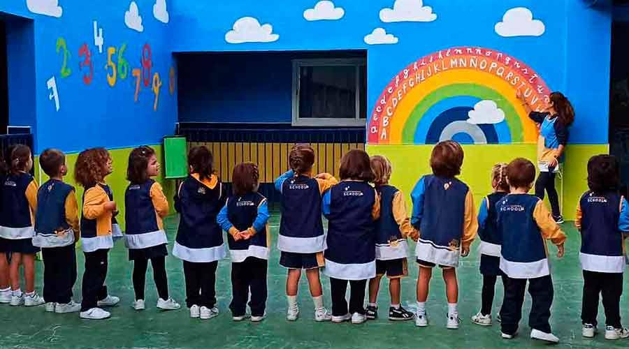 Chicos de primer ciclo de infantil alrededor de un arcoiris en la pared
