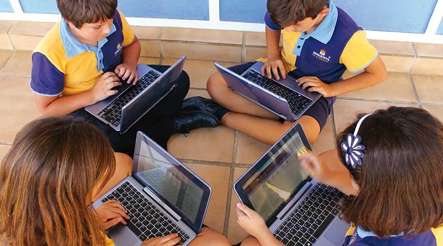 Cuatro estudiantes de primaria utilizando su ordenador portátil