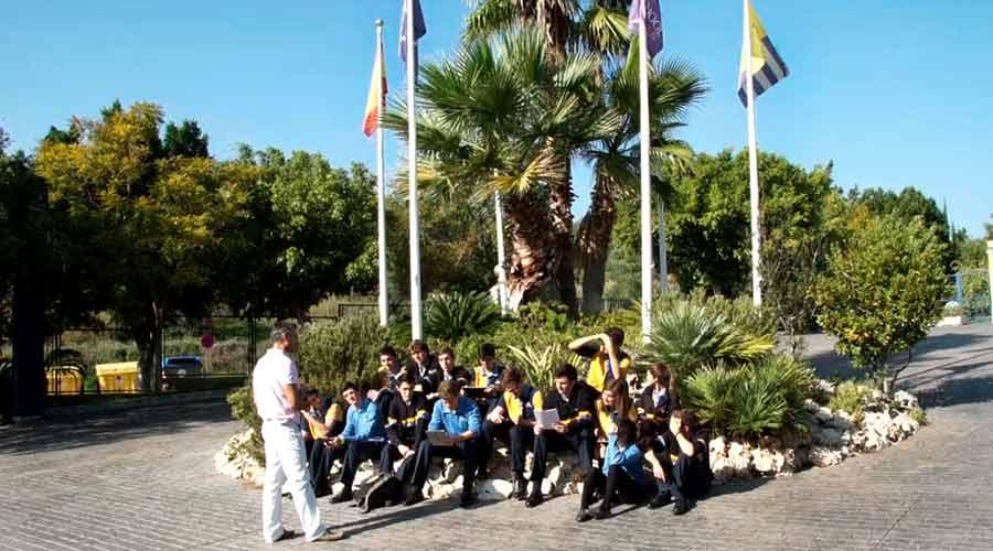 Grupo de estudiantes de secundaria sentados en el suelo