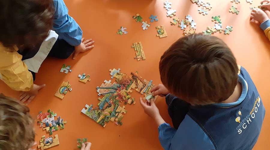 Alumnos inteligentes de infantil montando un puzle